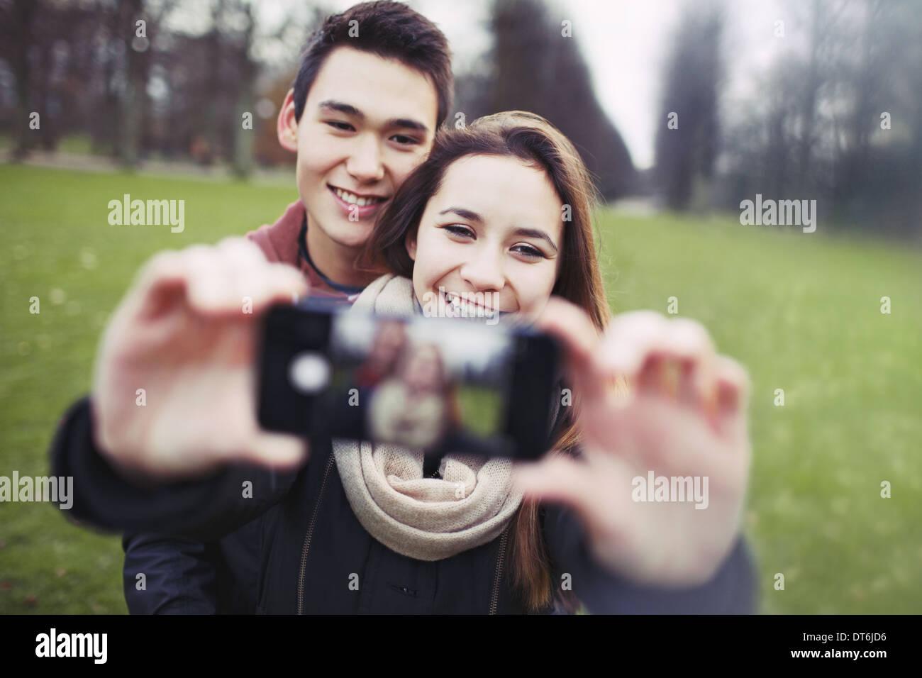 Pareja joven busca feliz mientras toma fotografías utilizando un teléfono inteligente en el parque. Adolescente y la chica enamorada de fotografiar. Imagen De Stock