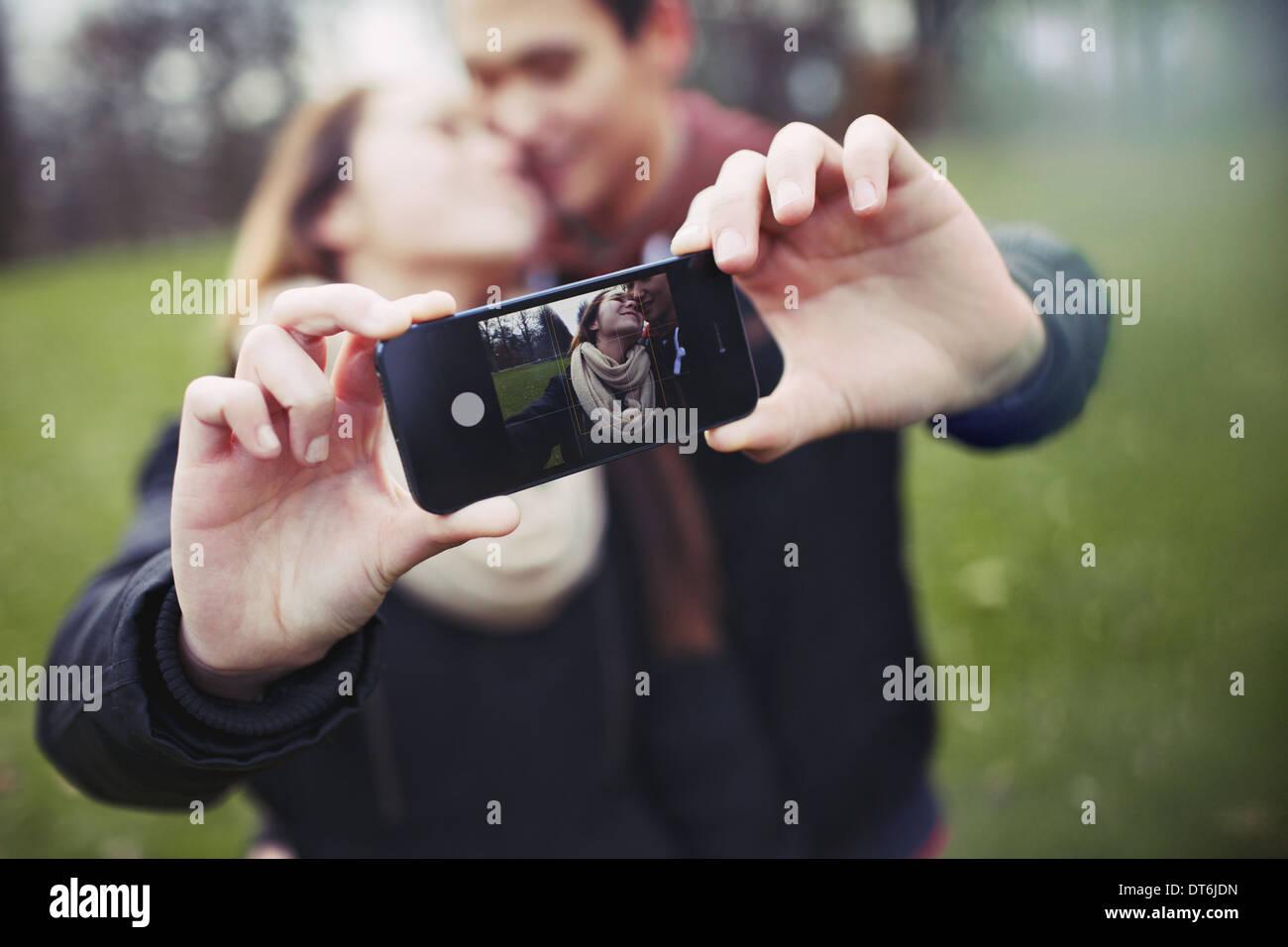 Romántica pareja de adolescentes tomando autorretrato con celular en el parque. Joven y de la mujer en el amor. Imagen De Stock