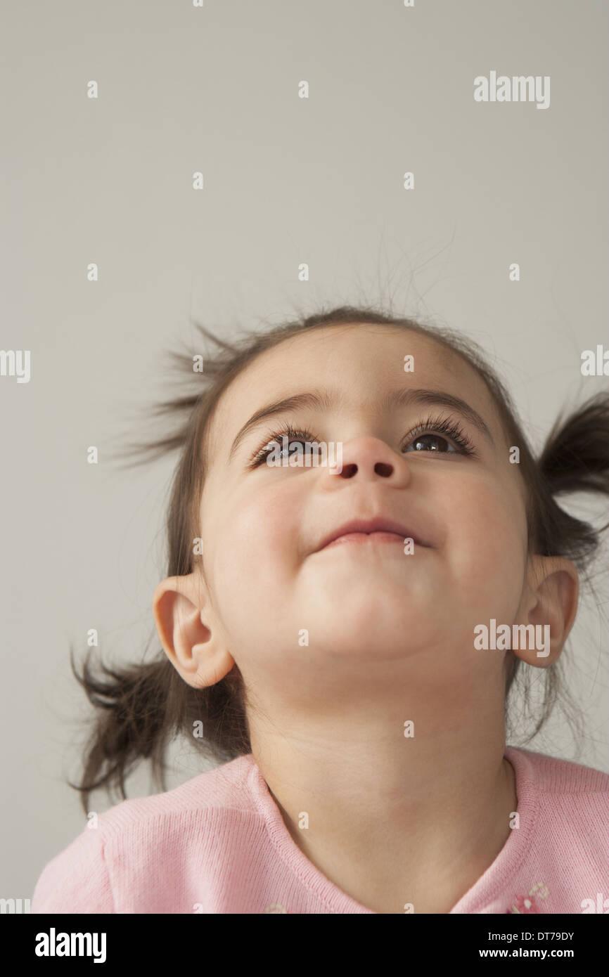 Una joven con ojos marrones y cabello oscuro en racimos. Mirando hacia arriba con la cabeza echada para atrás. Foto de stock