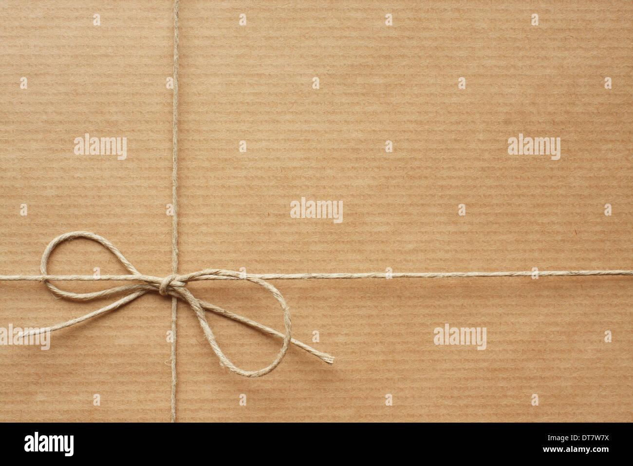 Pack envuelto en papel de envolver, atados con una cuerda. Espacio vacío para su texto Imagen De Stock