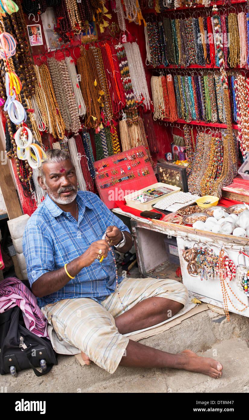 Hombre indio hacer collares y japamalas desde un almacén de la calle abierta. Puttaparthi, Andhra Pradesh, India Foto de stock