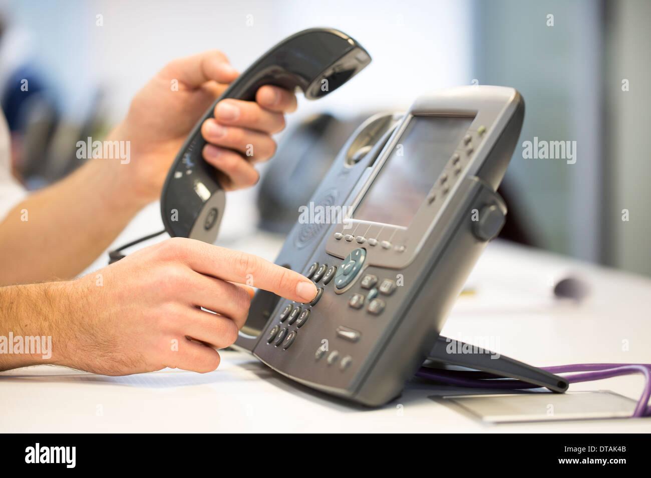 Close-up de manos del empresario tome el teléfono del gancho, en Office Imagen De Stock