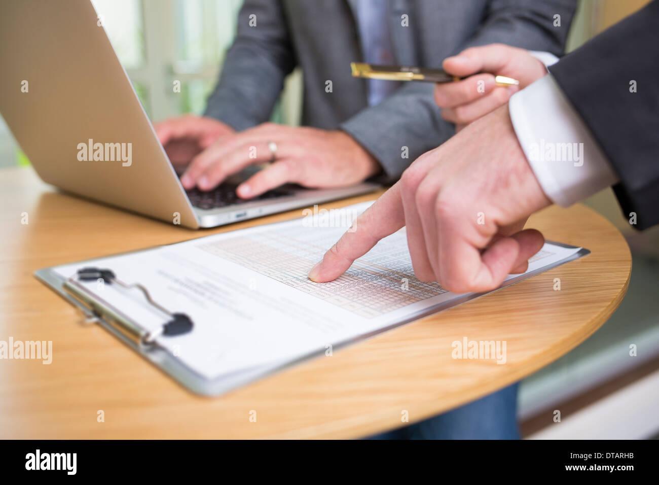 Acercamiento de las dos manos de empresarios que trabajan juntos en la oficina moderna con portátil Imagen De Stock