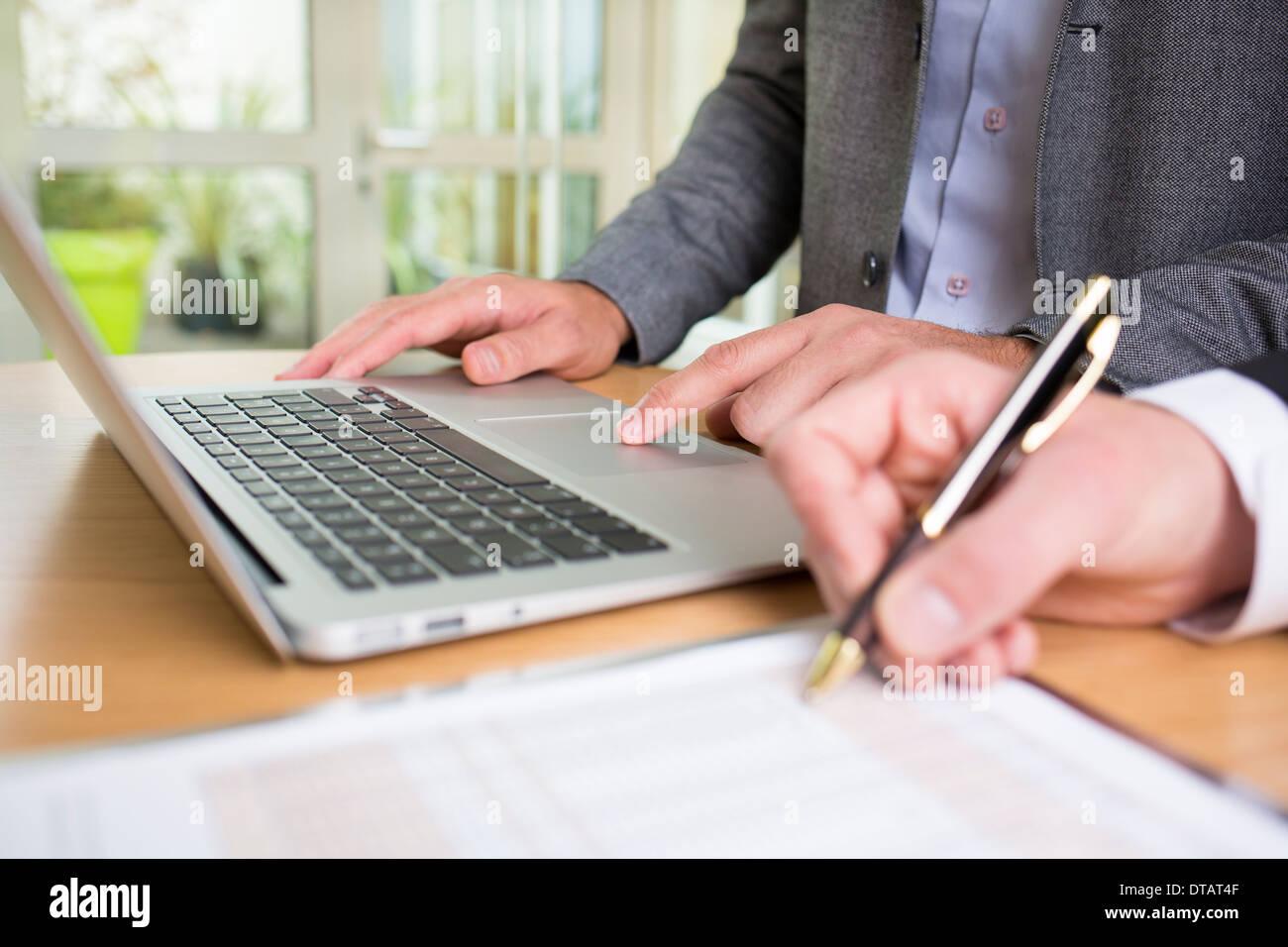 Acercamiento de las dos manos de empresarios que trabajan juntos en la oficina con el portátil Imagen De Stock