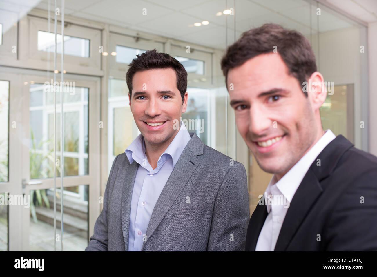 Retrato de dos empresarios sonrientes en oficina, mirando la cámara Foto de stock