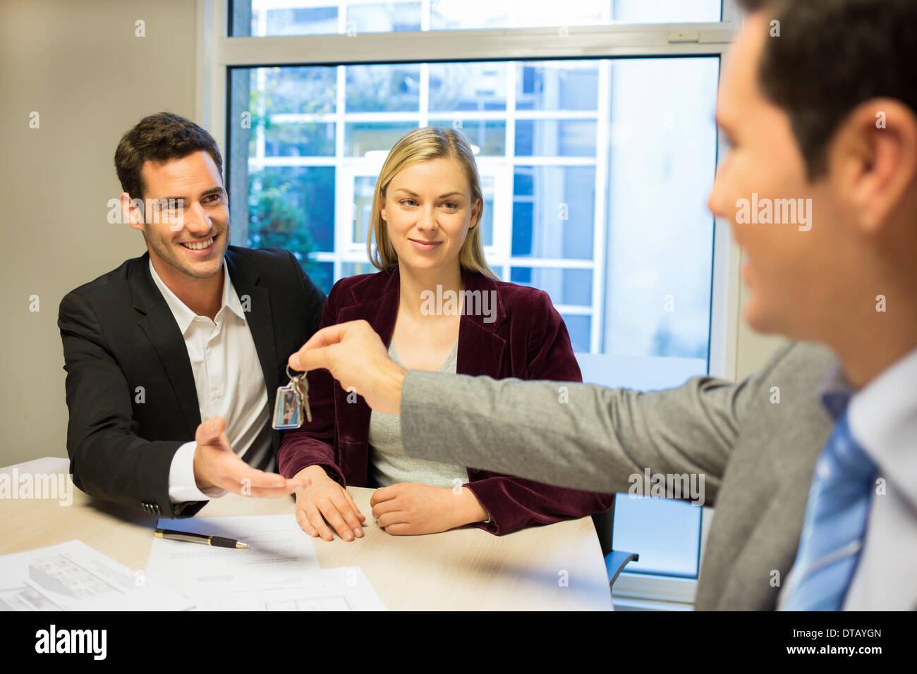 Inmobiliaria dando claves para nuevos propietarios Imagen De Stock