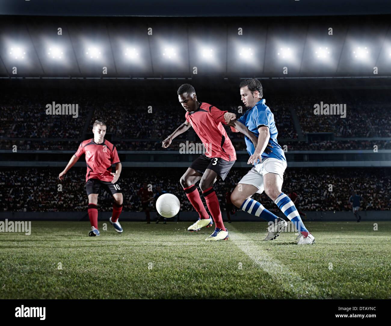Jugadores de fútbol con el balón en el campo Foto de stock
