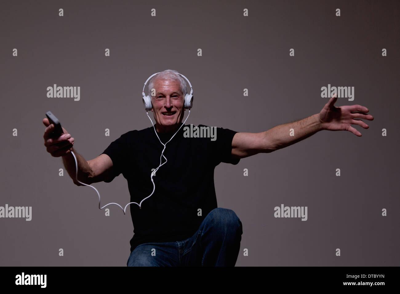 Retrato del hombre senior bailando en los auriculares del reproductor de MP3 Imagen De Stock