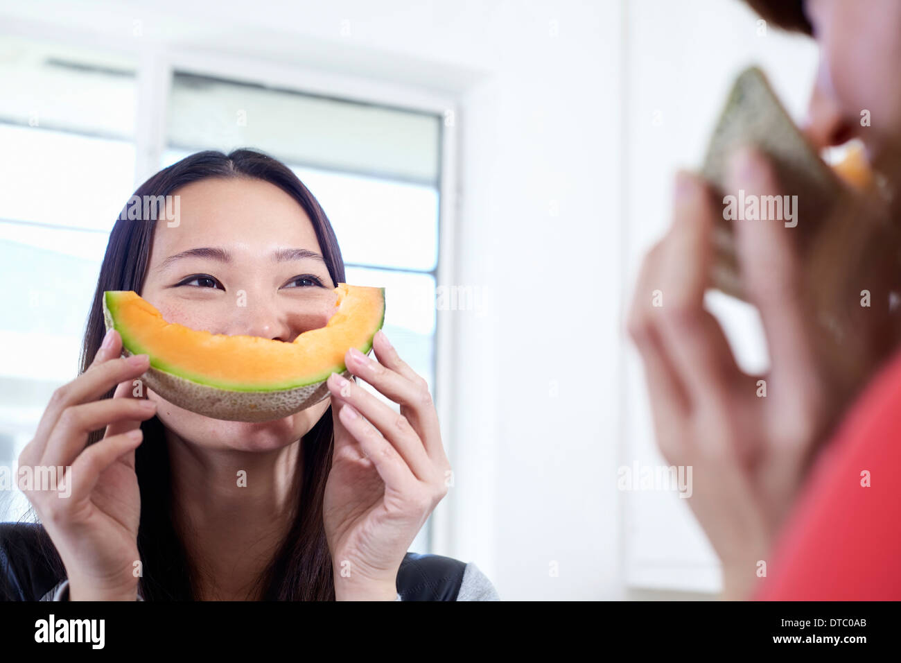 Dos jóvenes mujeres en la cocina con melón boca Imagen De Stock