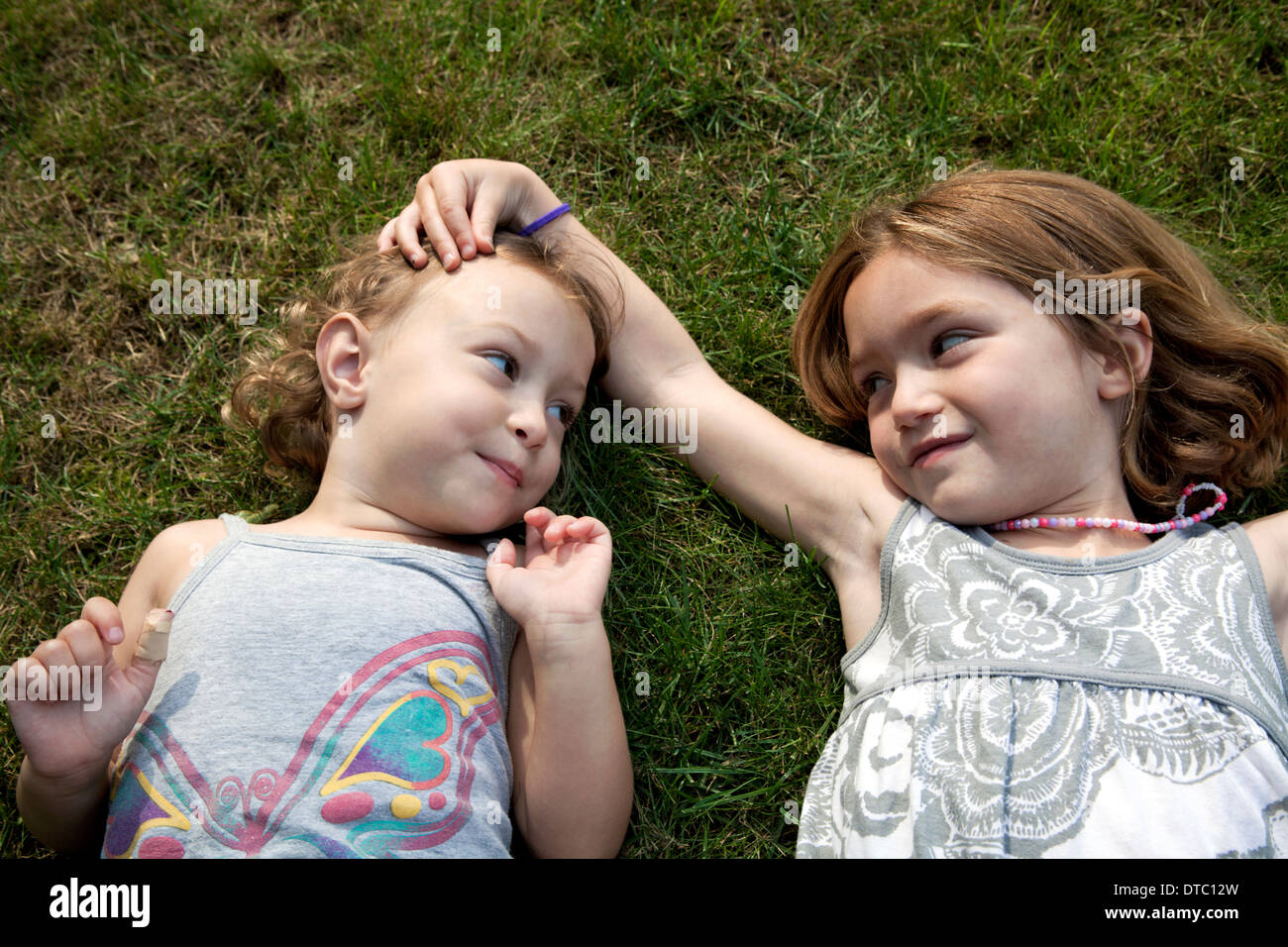 Retrato de dos jóvenes hermanas tumbado sobre el césped Imagen De Stock
