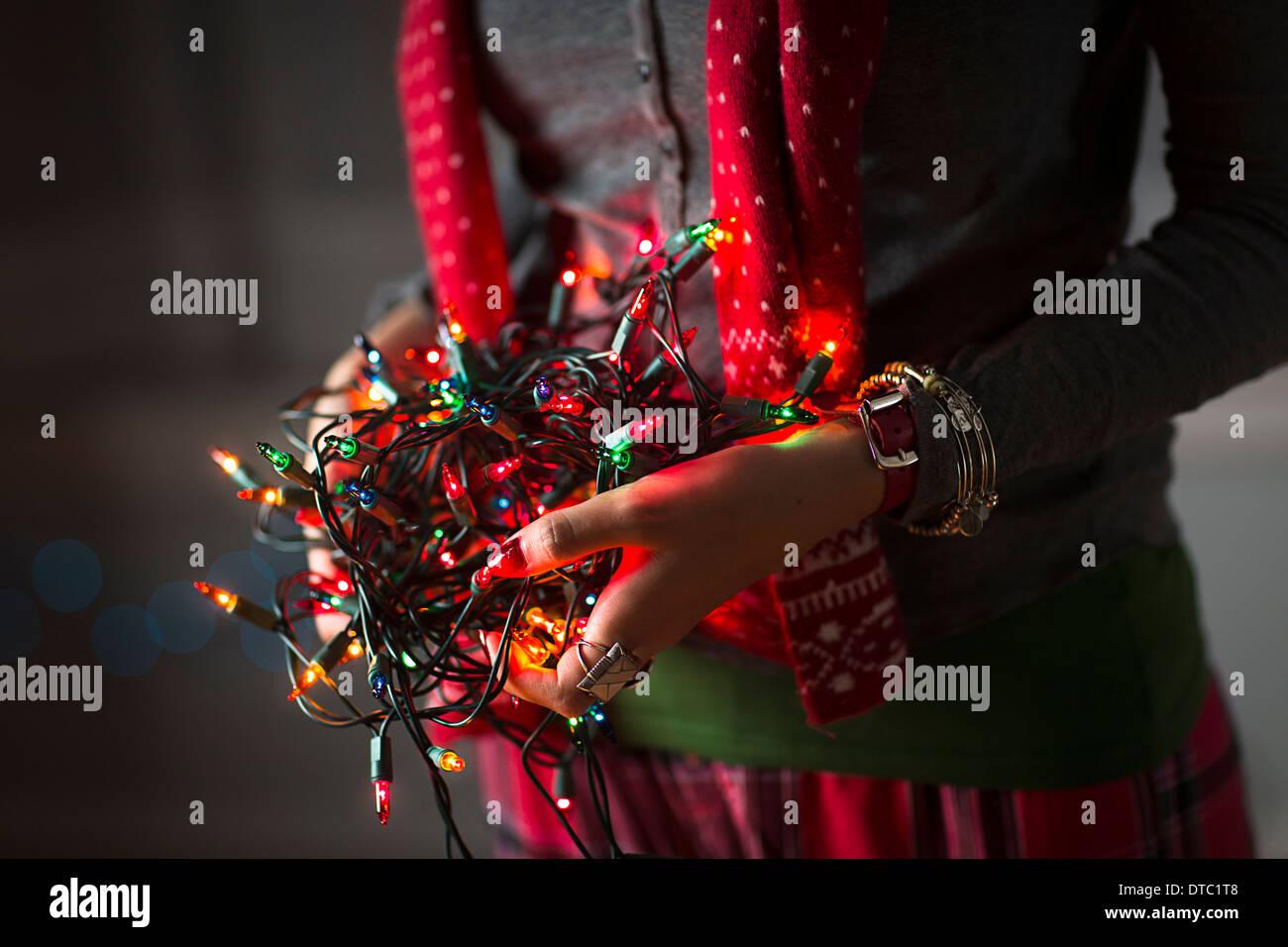 Cerca de joven mujer sosteniendo maraña de luces de Navidad Imagen De Stock