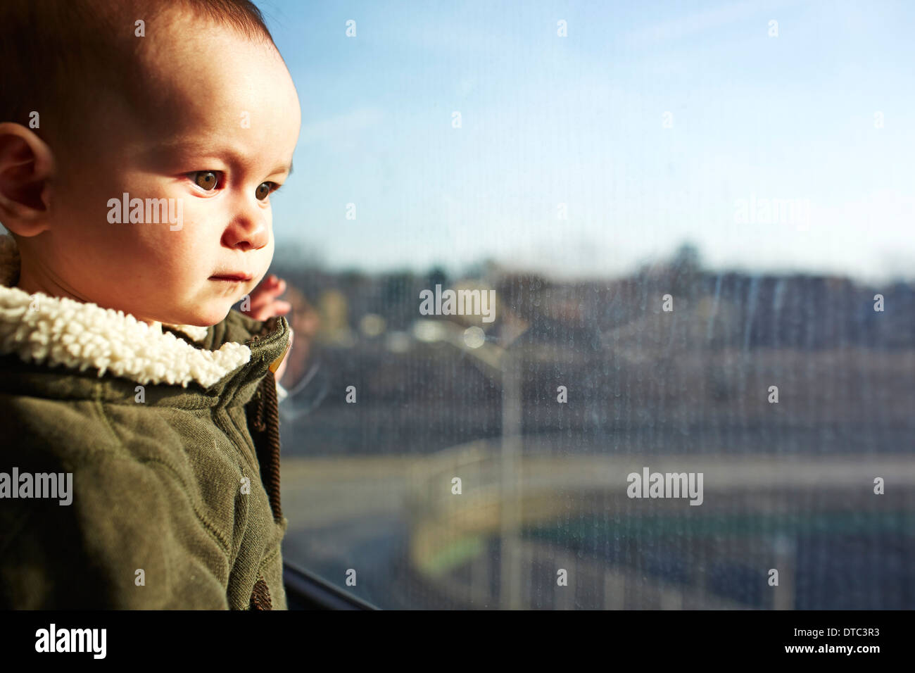 Cerca de Baby Boy mirando fuera de la ventana Imagen De Stock