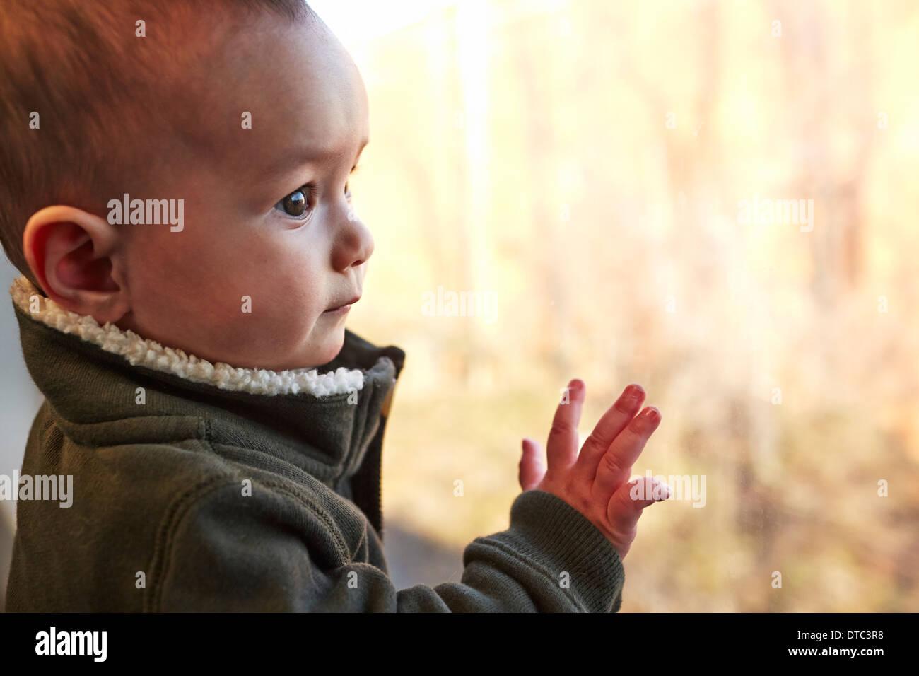 Cerca de Baby Boy mirando afuera de la ventana Imagen De Stock