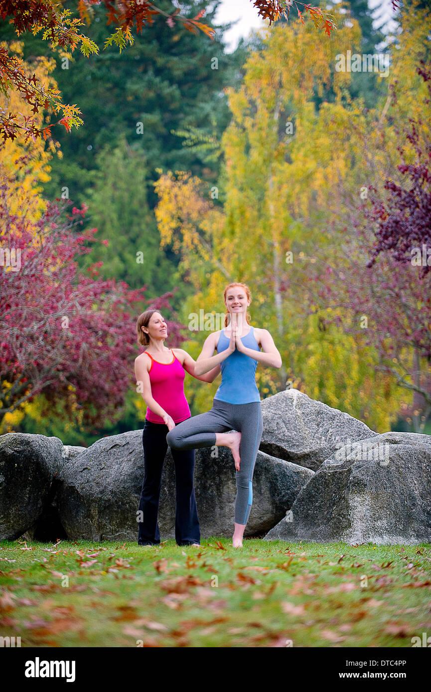 Instructor de Yoga mujer joven en el bosque Foto de stock