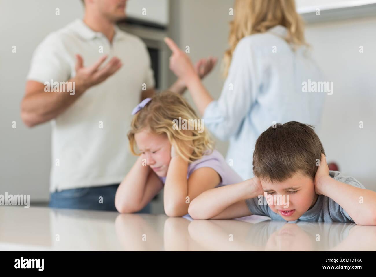 Los niños que cubren las orejas mientras los padres argumentando Imagen De Stock