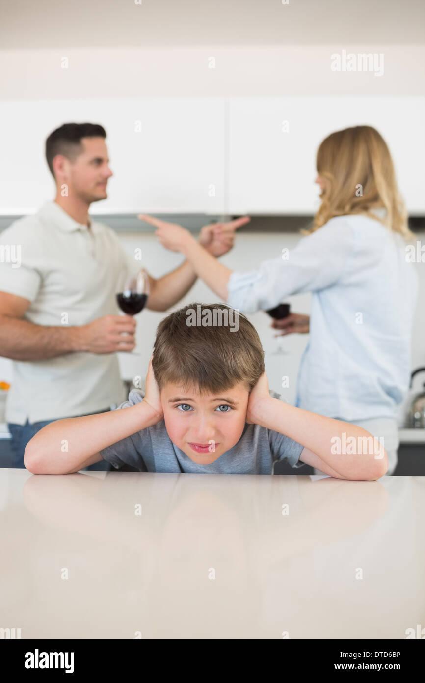 Muchacho que cubren las orejas mientras los padres argumentando Foto de stock