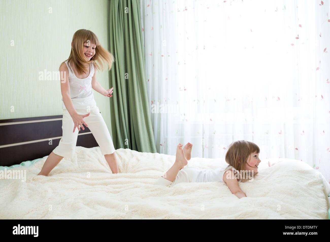 Dos hermanas jugando en la cama juntos Imagen De Stock