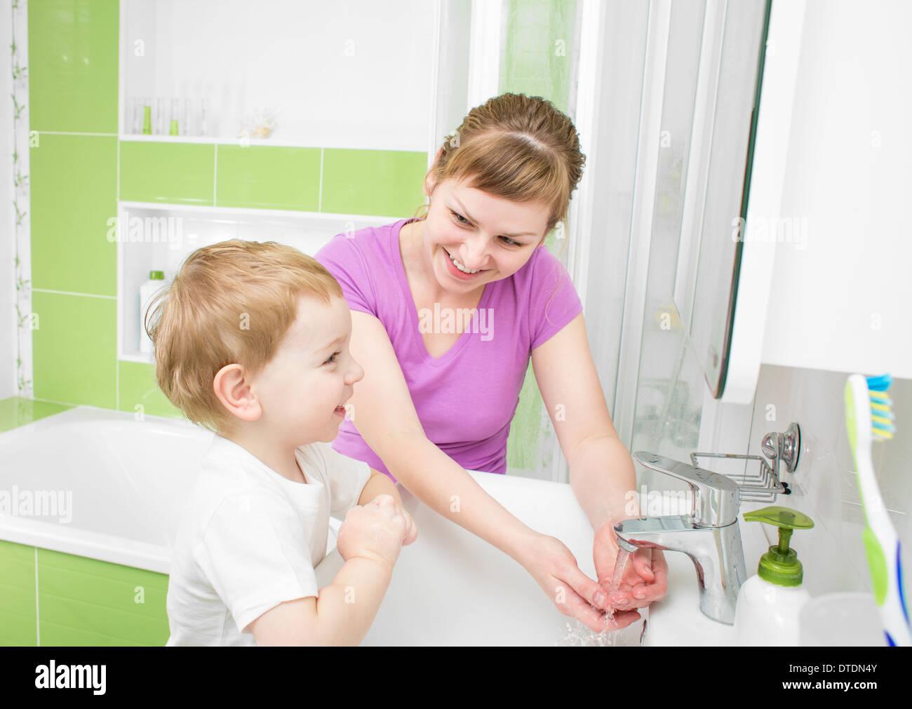 Feliz madre y kid el lavado de manos con jabón juntos en el baño. Foto de stock