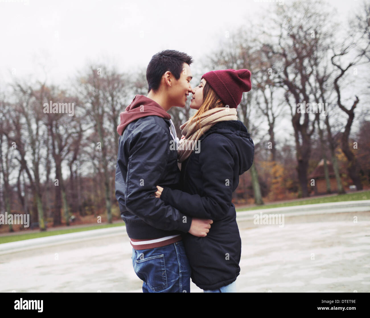 La pareja de adolescentes de raza mixta acerca de tener un apasionado beso en el parque. Apuesto joven y bella joven en ropa de abrigo. Imagen De Stock