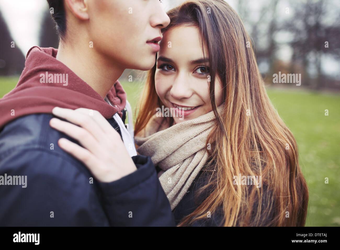 Hermosa chica adolescente con su novio en el parque. Pareja joven de raza mixta en el amor al aire libre. Imagen De Stock