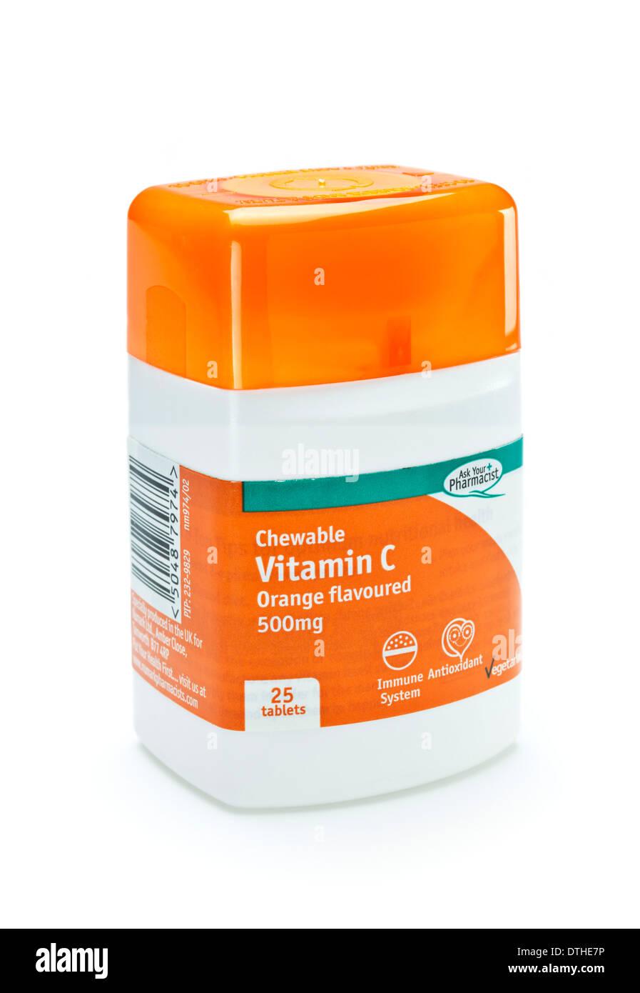 Las tabletas masticables de vitamina C en un frasco sobre un fondo blanco. Imagen De Stock