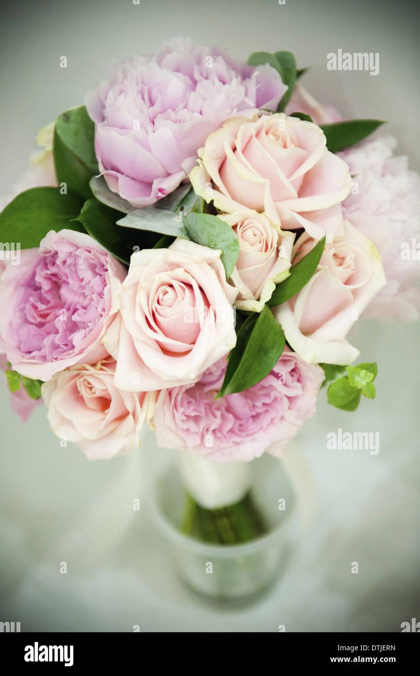 Un ramo de rosas color rosa pastel y lavanda pálido peonías con pequeñas hojas verdes de Inglaterra Foto de stock