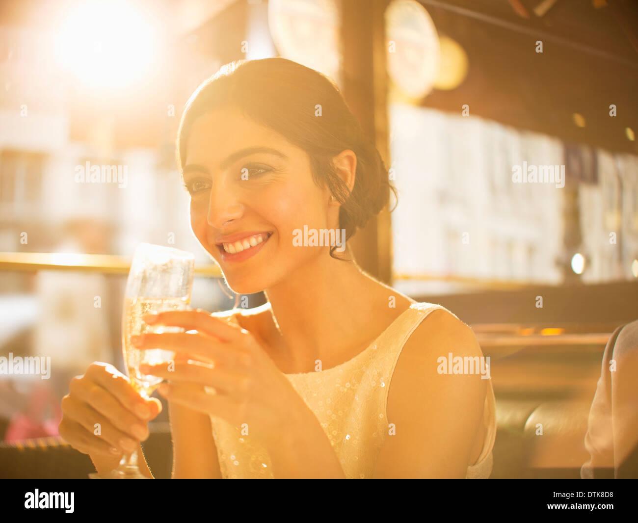 Bien vestida mujer beber champán en el restaurante Imagen De Stock