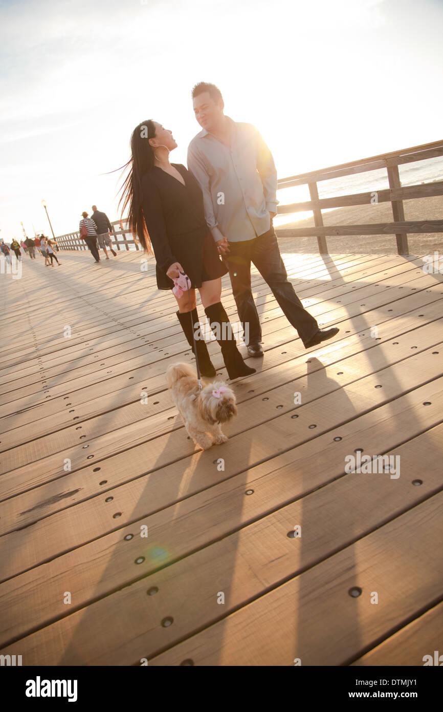 Pareja asiática en la playa con su perro en el pier compartir besos y abrazos y mucho amor. Imagen De Stock