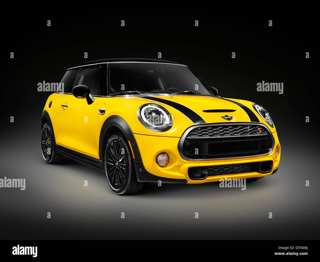 Amarillo 2014 Mini Cooper S, Mini Berlina bicuerpo, ciudad compacta coche aislado sobre fondo negro Imagen De Stock