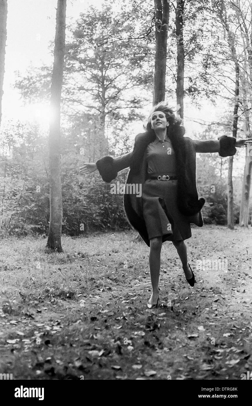 1960 modelo de pasarela con abrigo corriendo en el bosque Imagen De Stock