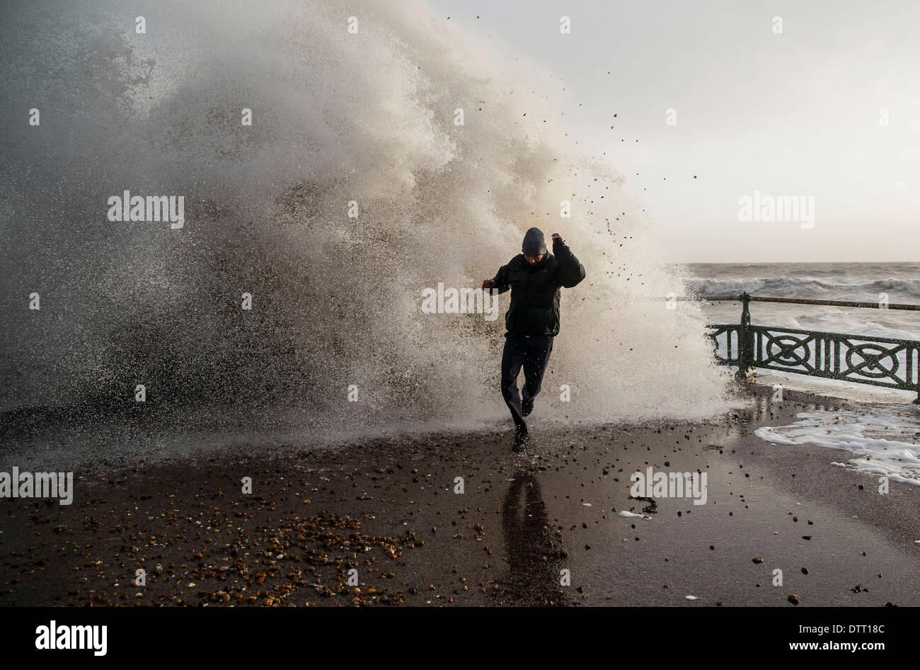 Un hombre va desde las enormes olas durante las marejadas en las costas británicas en condiciones meteorológicas extremas. Escena en Brighton, Sussex, Reino Unido Foto de stock