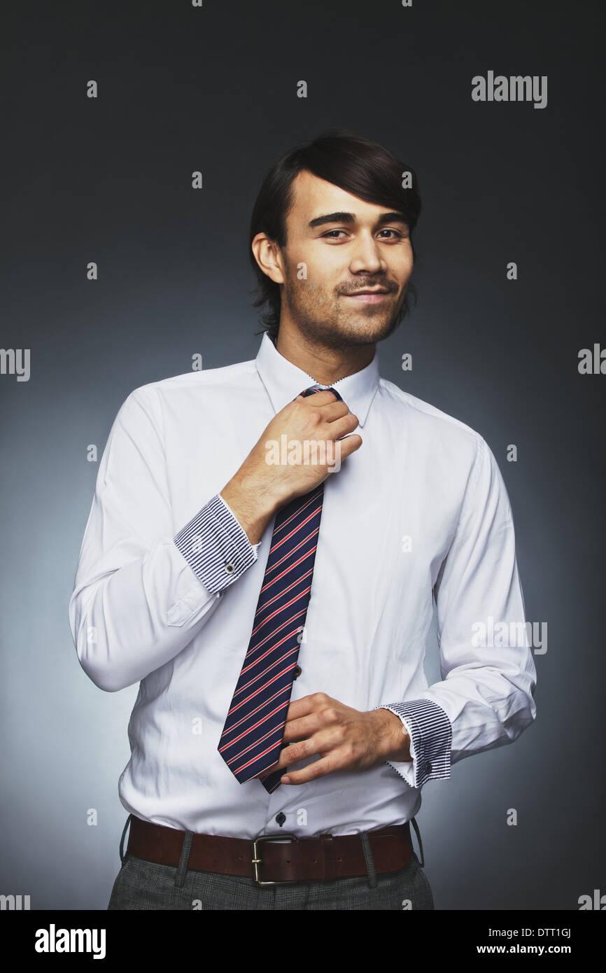 Joven empresario inteligente ajustando su corbata mirando a la cámara sonriendo. Raza mixta modelo masculino preparándose para la oficina. Imagen De Stock