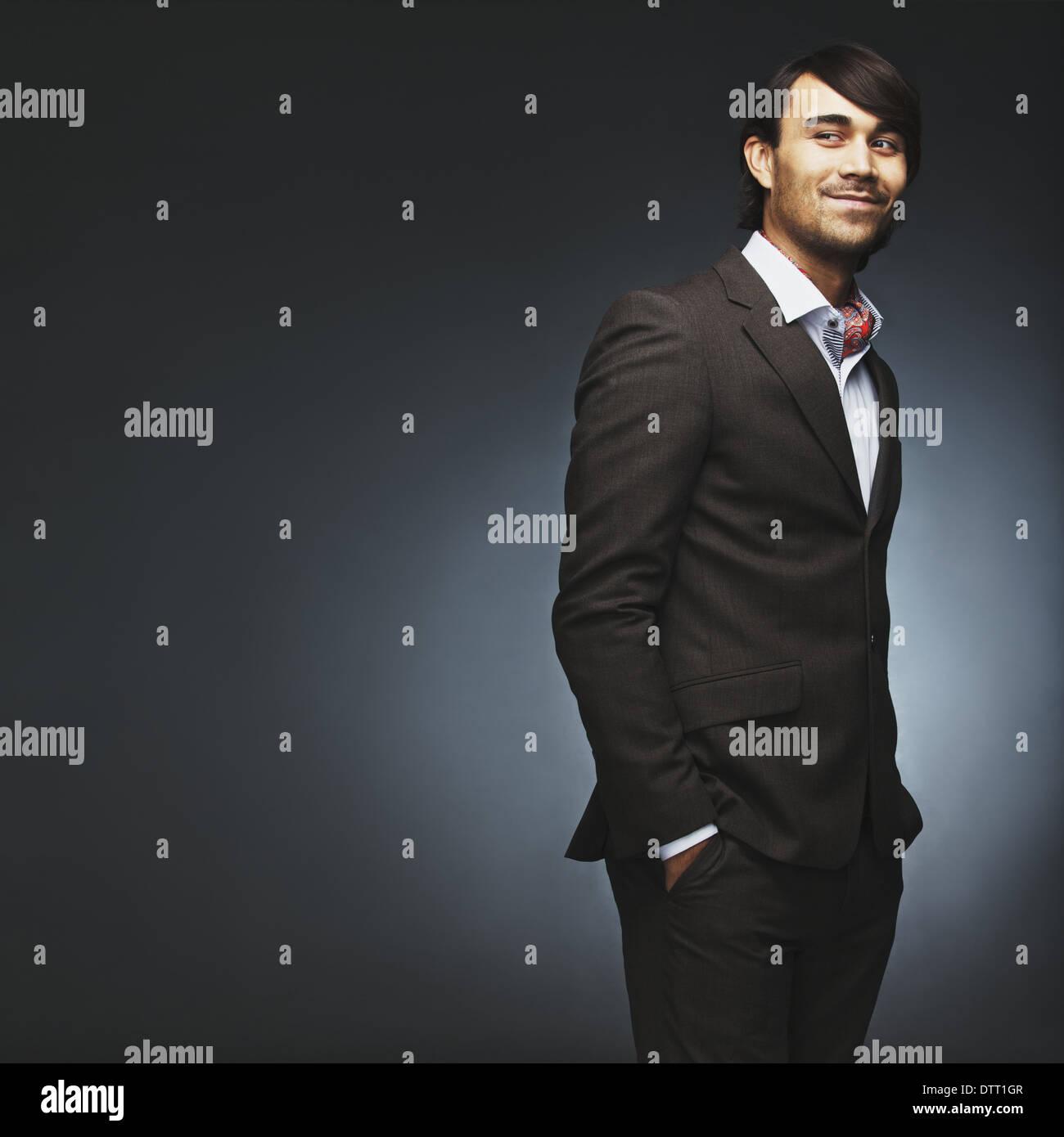 Joven atractivo llevar traje de pie con sus manos en el bolsillo mirando por encima del hombro. Guapo modelo moda masculina posando. Imagen De Stock