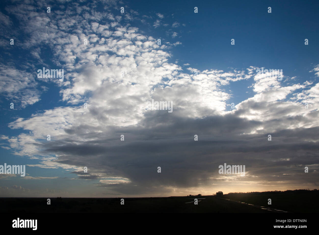 Nubes frontales moviéndose sobre el cielo bloqueando el sol en Bawdsey, Suffolk, Inglaterra Imagen De Stock