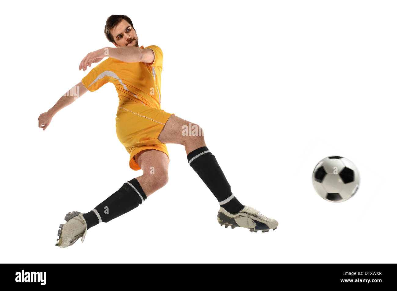 Jugador de fútbol Patea la bola en mitad del aire aislado sobre fondo blanco.  Imagen ff73db4a7820a