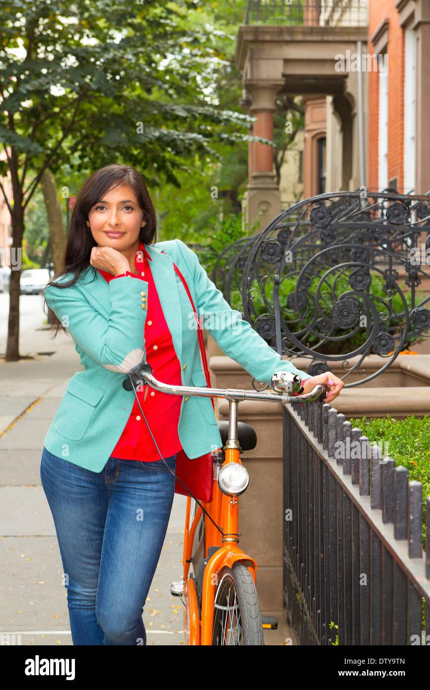 Mujer de raza mixta con bicicleta, Brooklyn Heights, Nueva York, Estados Unidos Foto de stock