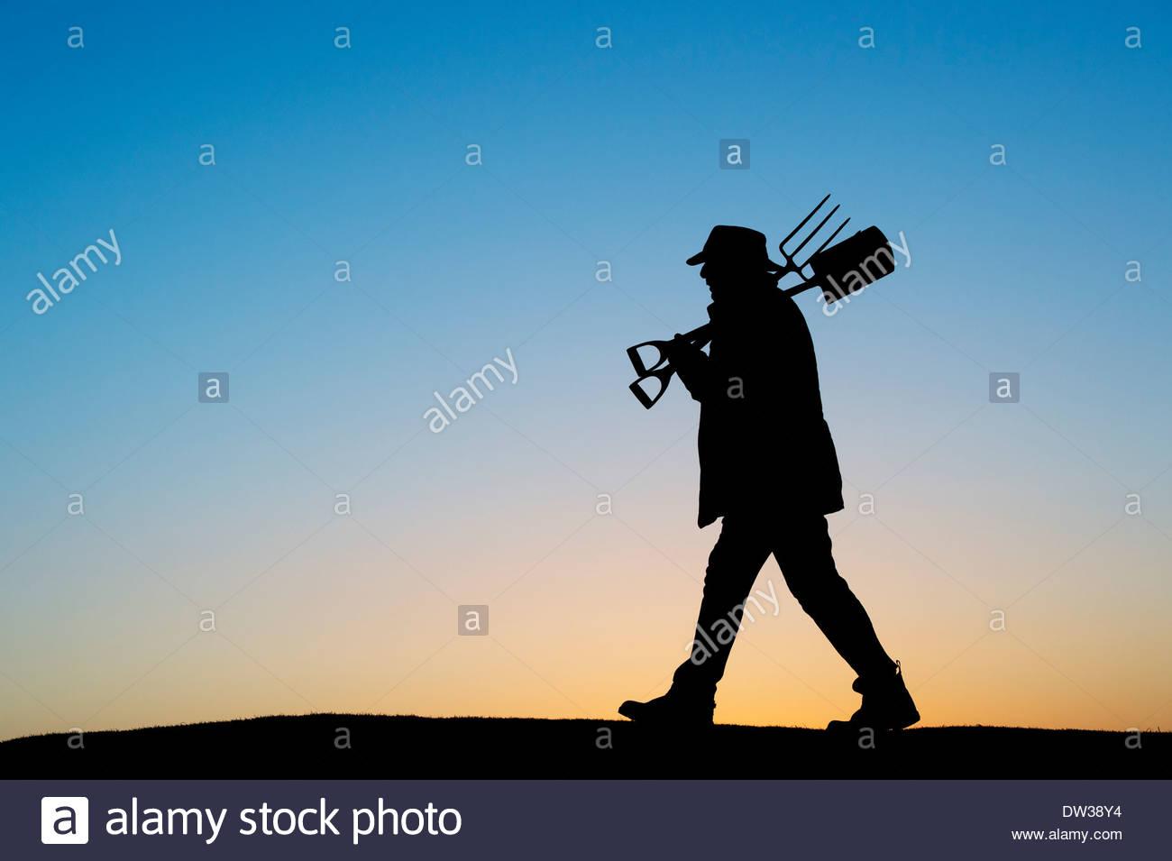 Jardinero caminando con una pala y horquilla. Silueta Imagen De Stock
