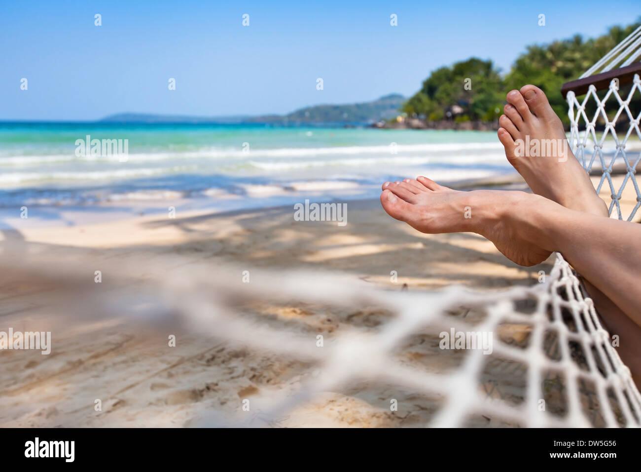 Mujer pies en una hamaca en la playa Imagen De Stock
