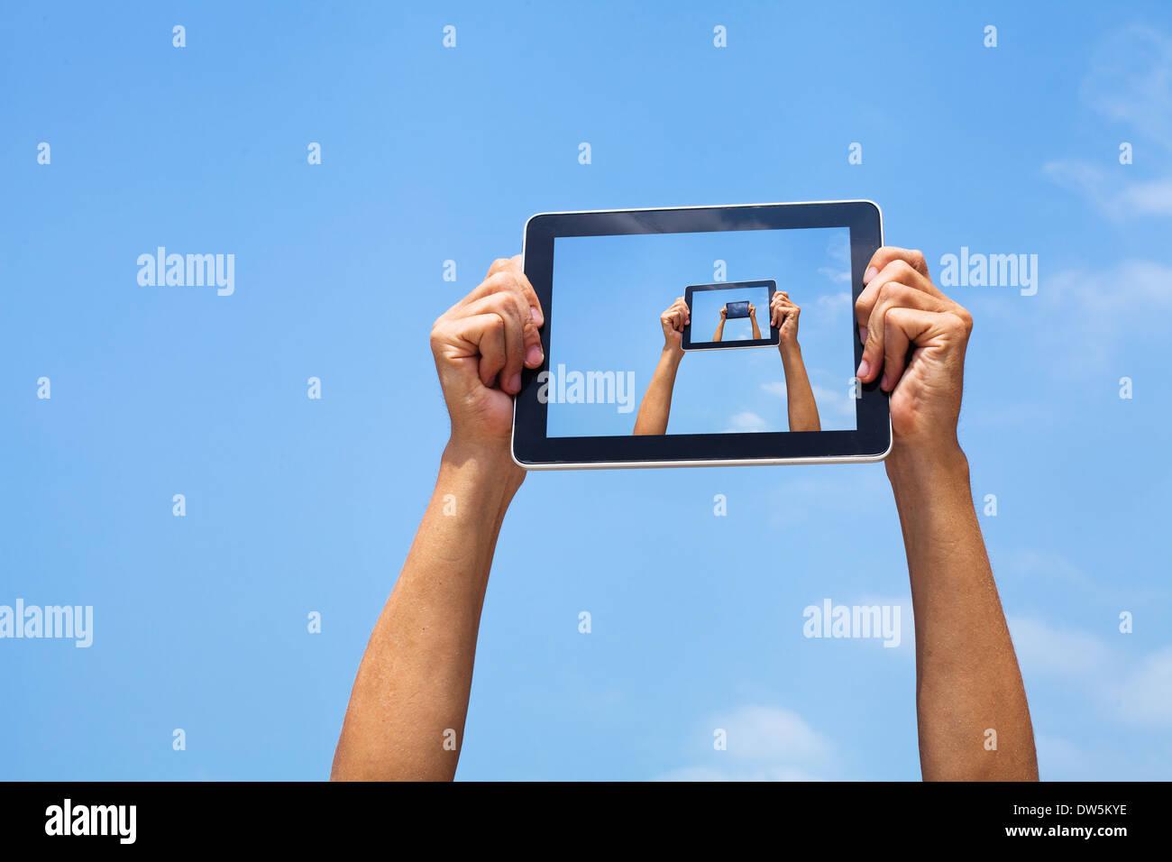 Manos sosteniendo tableta en blue sky Imagen De Stock