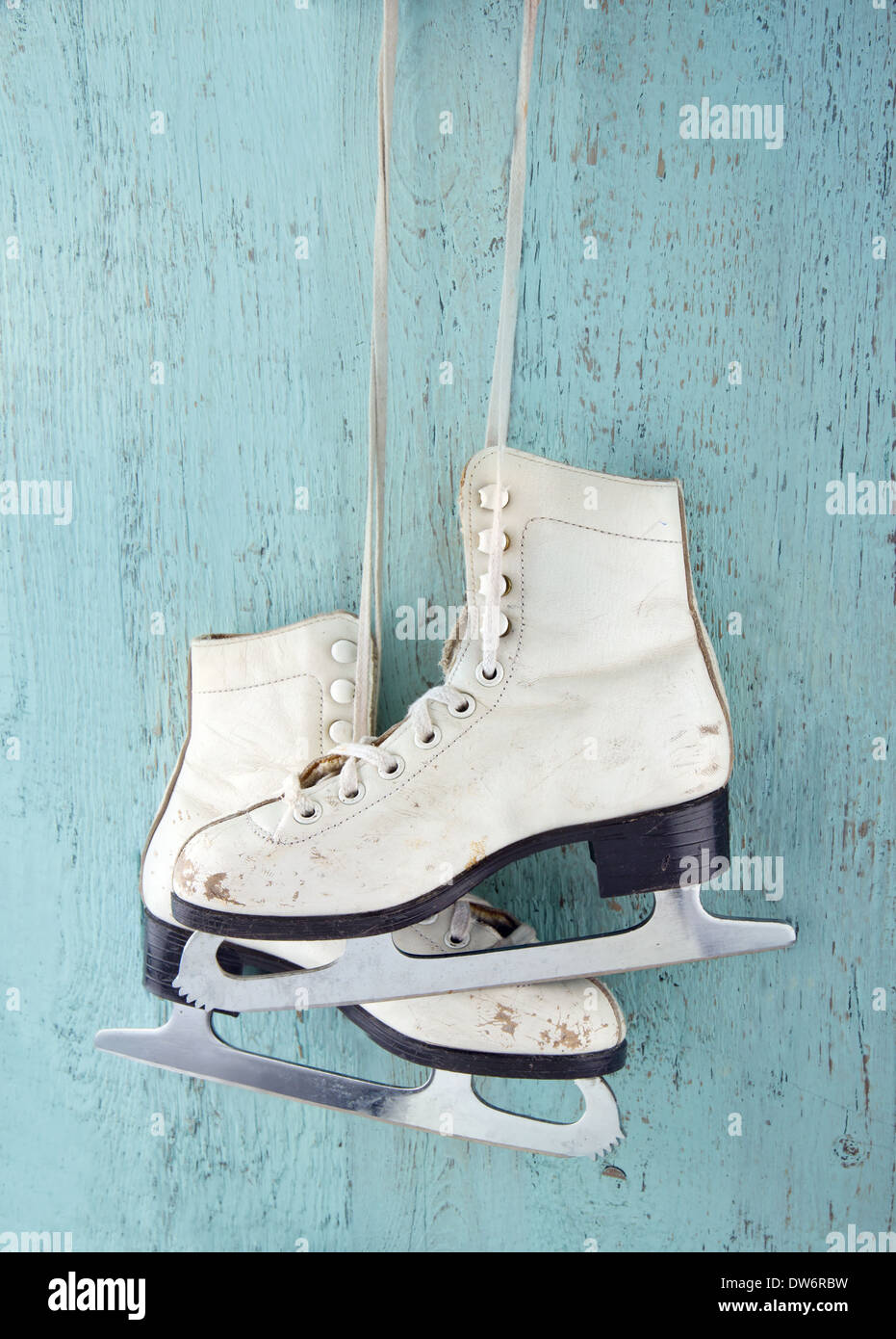 Par de patines de hielo la mujer blanca sobre fondo azul de madera vintage - femenino concepto deportes de invierno Imagen De Stock