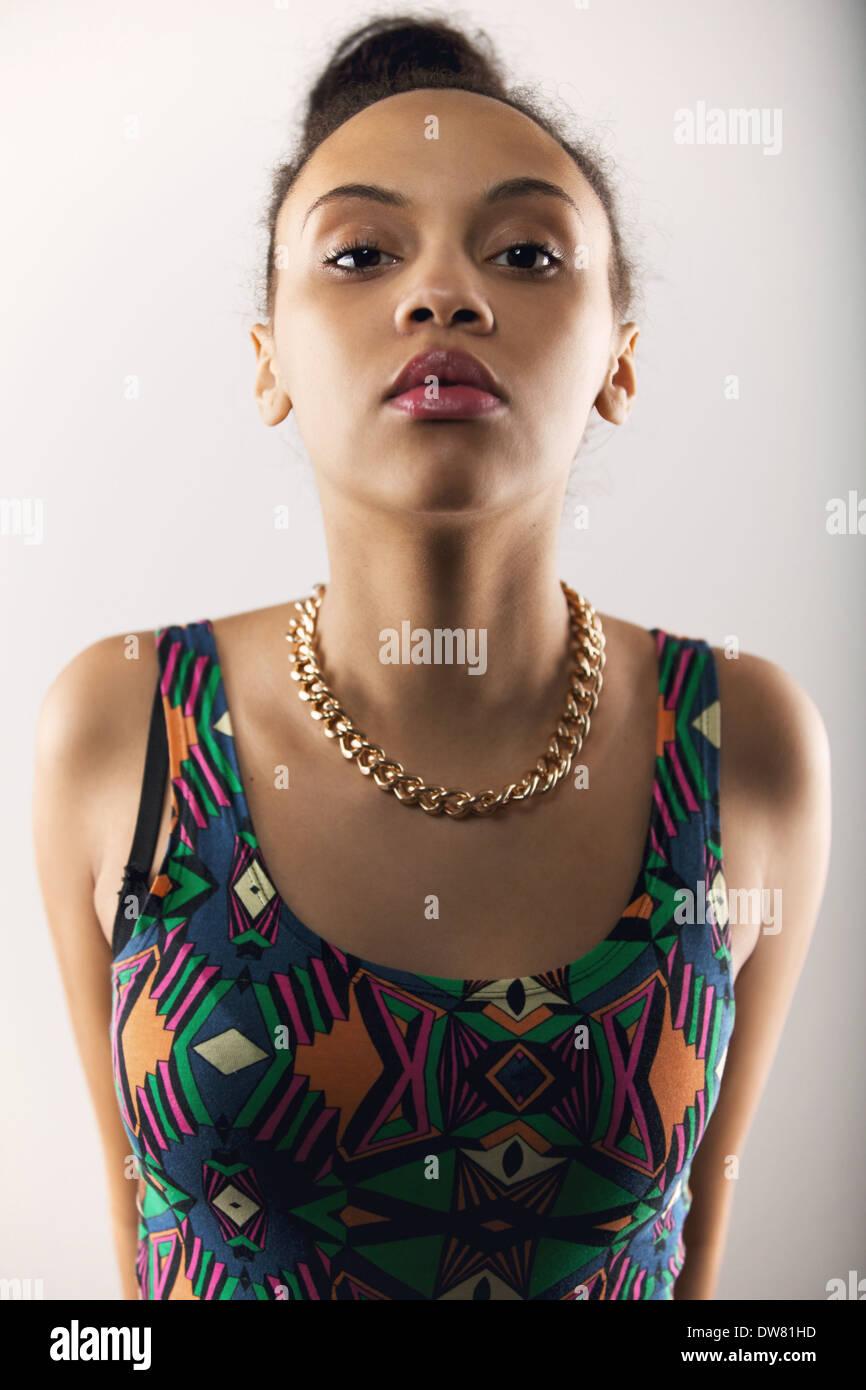 Retrato de mujer joven mirando a la cámara con una actitud. Modelo de mujer hermosa posando sobre fondo gris Imagen De Stock