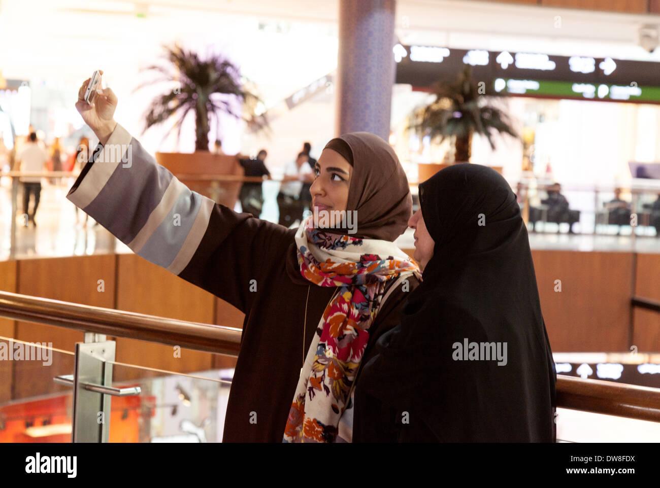 Dos mujeres árabes musulmanes tomando un selfie en un teléfono móvil, el centro comercial Dubai, EAU, Emiratos Arabes Unidos, Oriente Medio Imagen De Stock