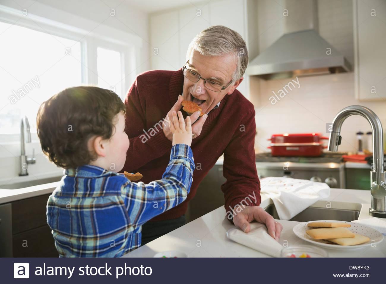 Alimentación niño galletas navideñas al abuelo Imagen De Stock