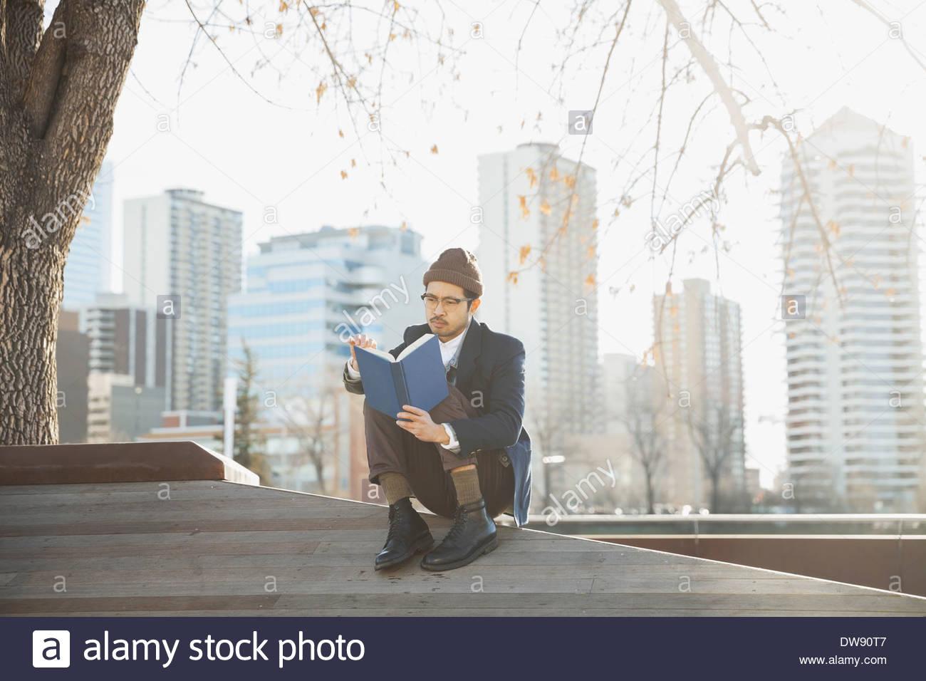 El hombre libro de lectura al aire libre contra el paisaje urbano Imagen De Stock