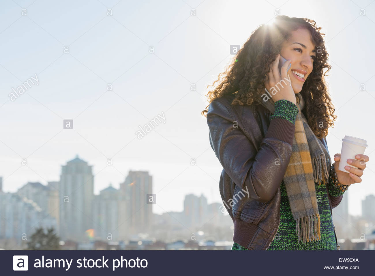 Mujer sonriente Contestar teléfono inteligente contra el paisaje urbano Imagen De Stock