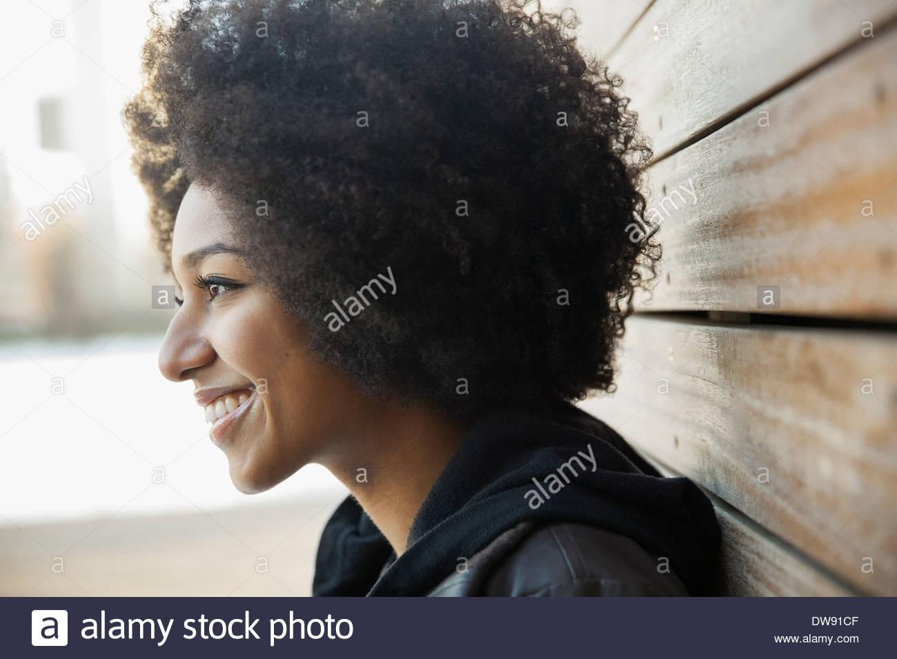 Vista lateral de la mujer sonriente al aire libre Imagen De Stock