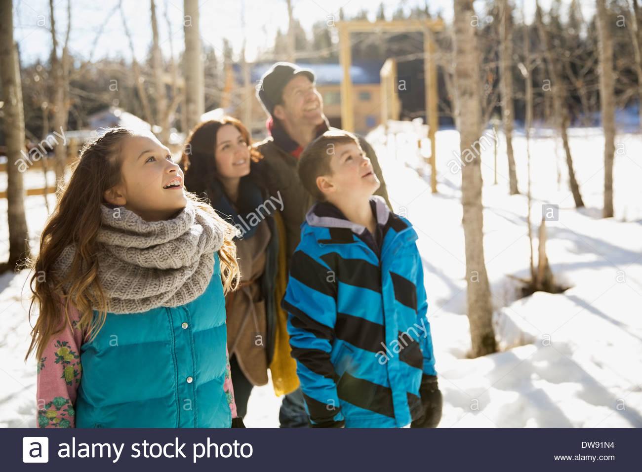 Familia mirando hacia arriba en el bosque nevado Imagen De Stock