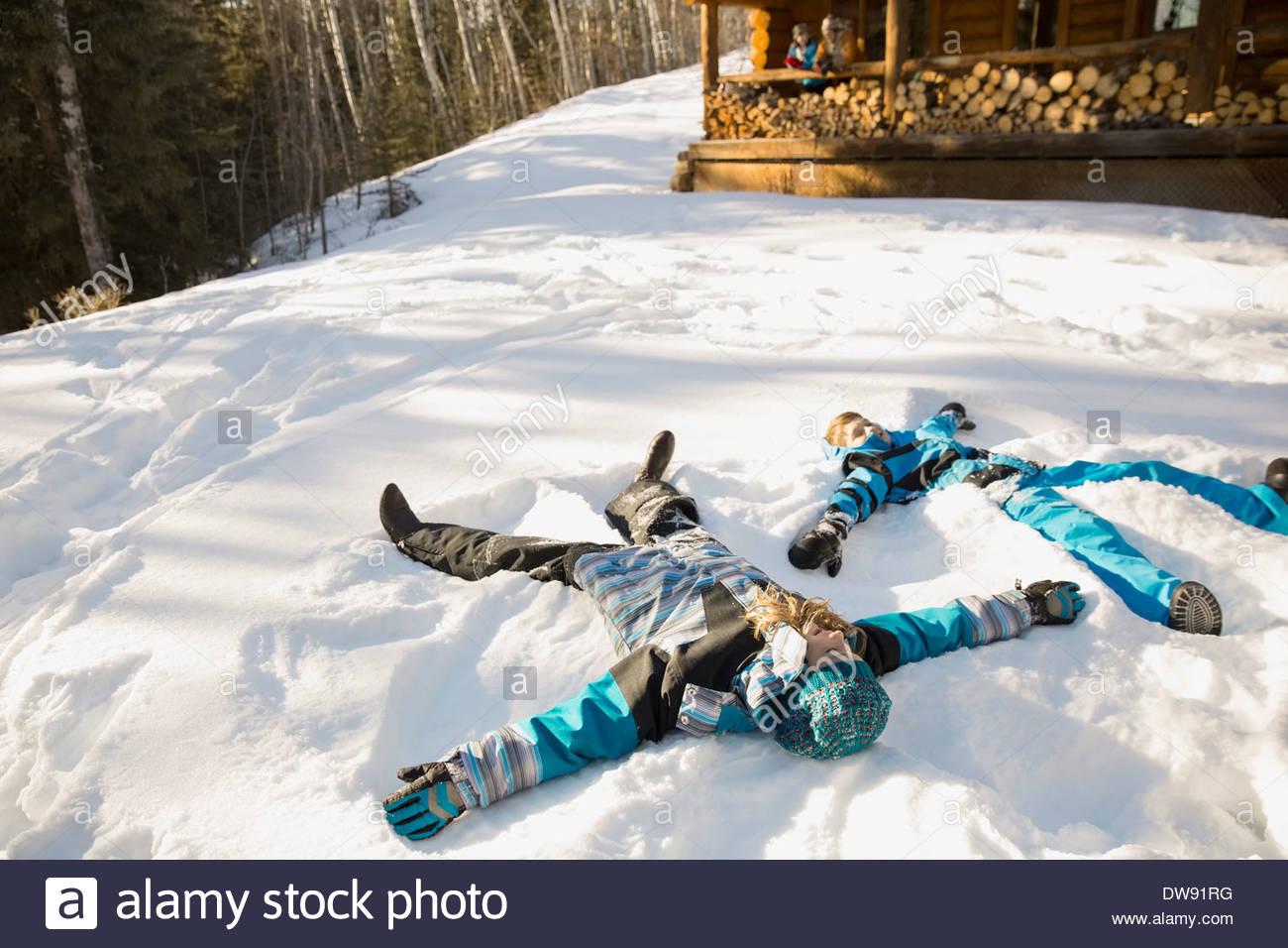 Hermanos haciendo ángeles de nieve Imagen De Stock
