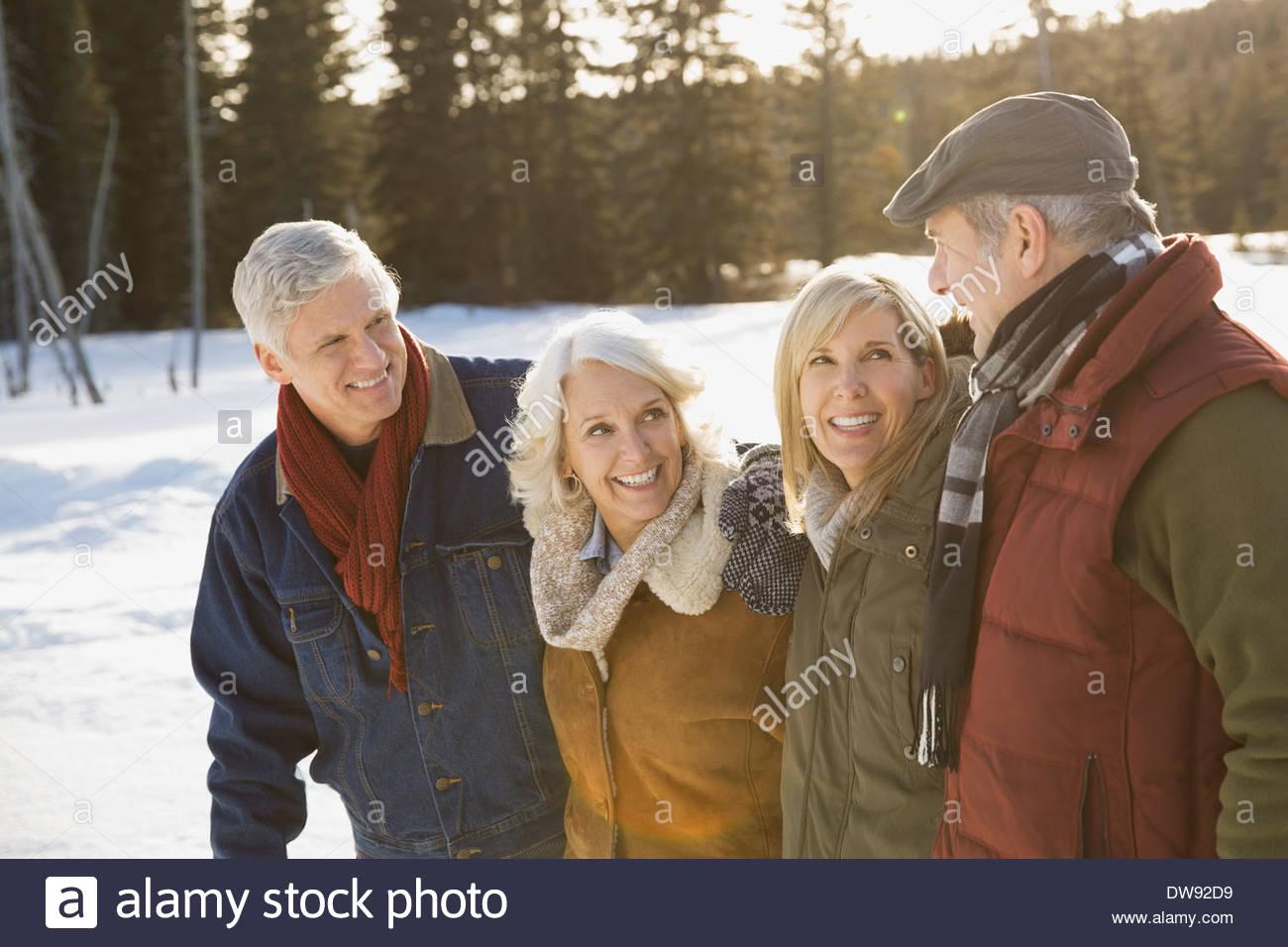 Sonrientes amigos maduros de pie afuera en invierno Imagen De Stock