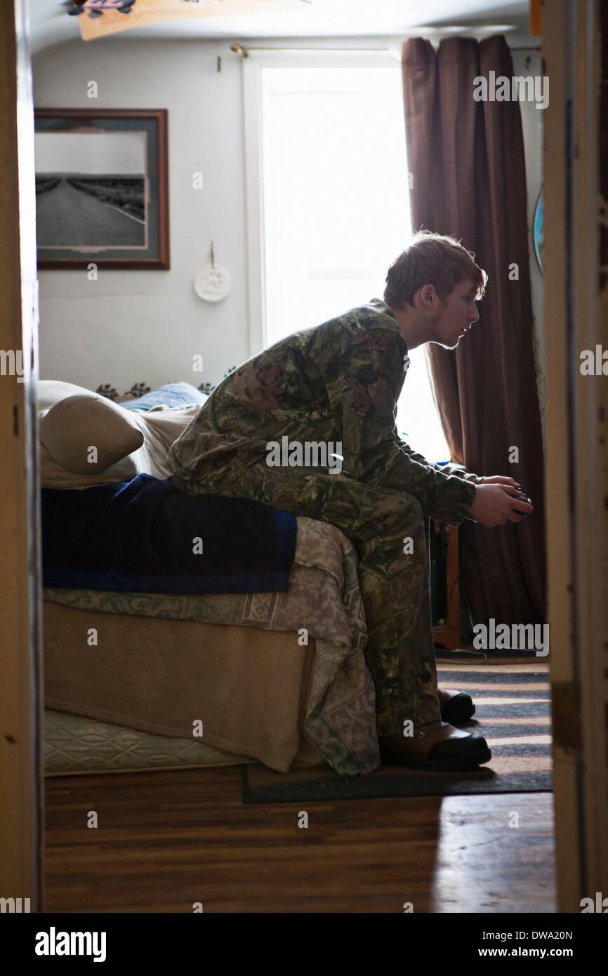 Adolescente sentado en el sofá concentrando en video juego Foto de stock